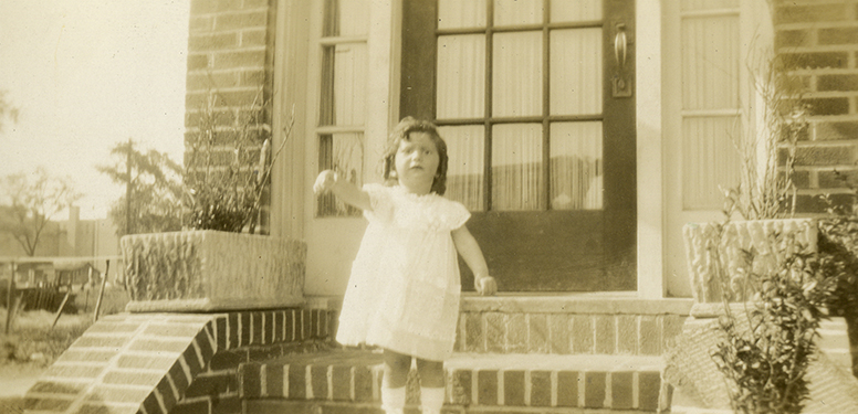 Toddler girl in dress standing on brick steps waving good bye.