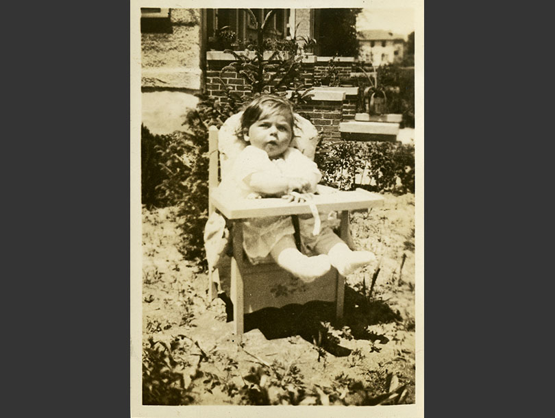 An 8-month girl sitting outside in a small wooden chair that has a little attached shelf in front.