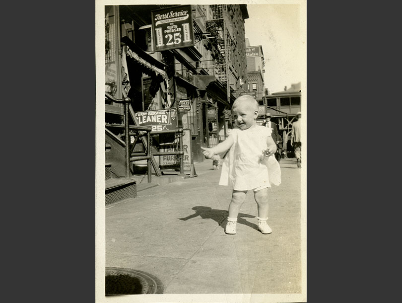 An 11-month White girl standing on a street in 1930s New York, signs for businesses in background.