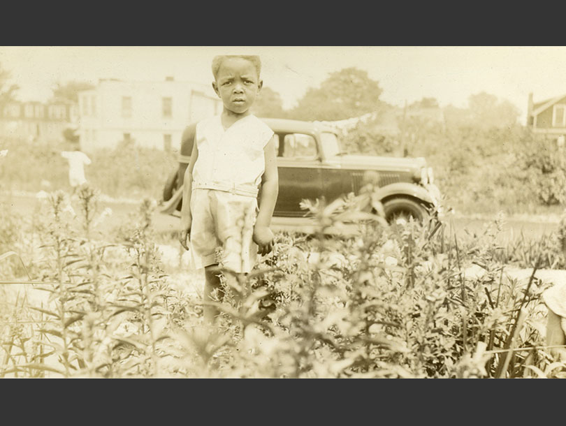 African American toddler boy in shorts standing in a field, 1930s Ford and houses in the background.