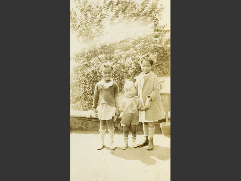 Two African American girls standing next to an African American toddler boy on an outside terrace.
