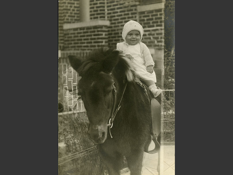 Baby in a crocheted cap sitting on a saddled pony.