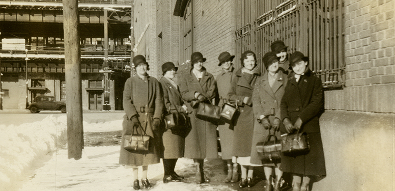 Seven White female nurses pose outside in matching cloche hats and overcoats, snow on the ground.