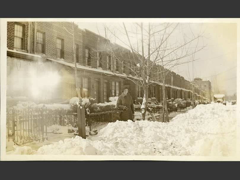 A White female nurse standing in the snow in front of row homes in the city.