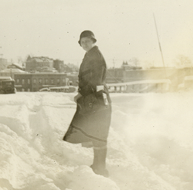 Nurse in coat and cloche hat standing in foot-high drifts of snow, buildings in distance.