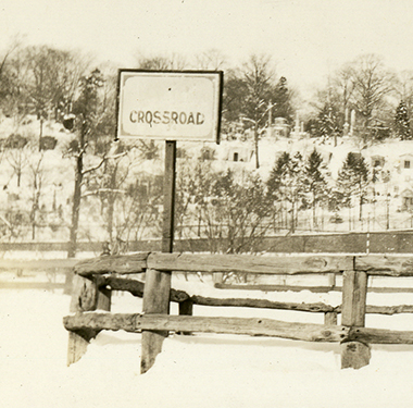 Snowy roadside with a split-rail fence and a cemetery up a low hill beyond.
