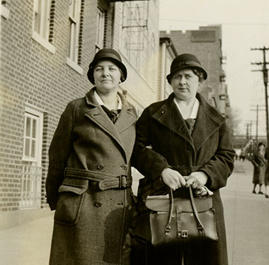 Two, White female nurses in cloche hats and overcoats standing on a sidewalk near a building.