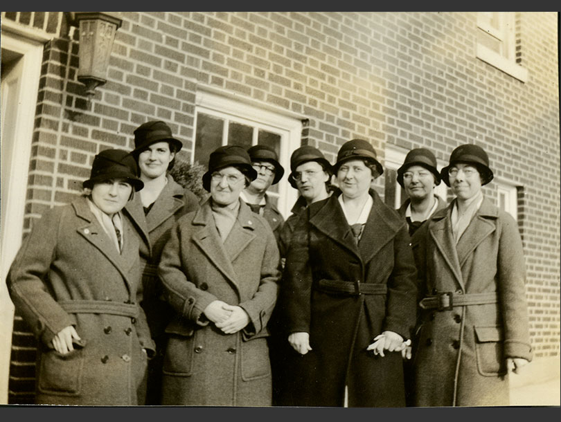 8 smiling, White female nurses in overcoats and cloche hats outside a brick building.