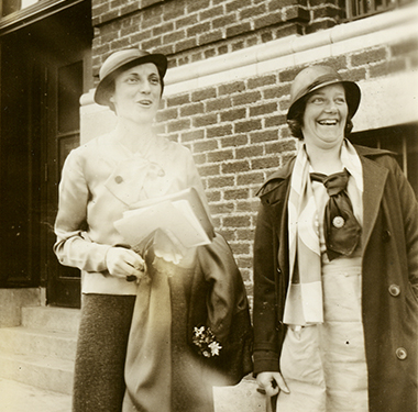 Two, White females in cloche hats standing near a brick building. Miss Giles is in uniform.