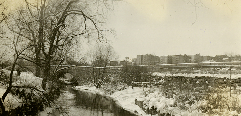 Small stone bridge arching over snowy banks of a narrow stream, apartments in far distance.