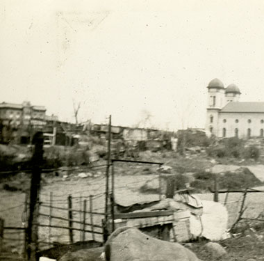 Two-towered church rising in distance beyond a lot jumbled with shacks and various fences.