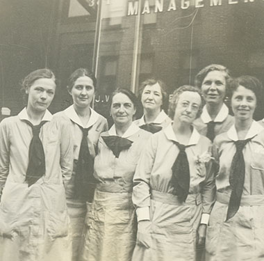 8 White, female nurses in uniform dresses with double front pockets and neck ties in front of a building.