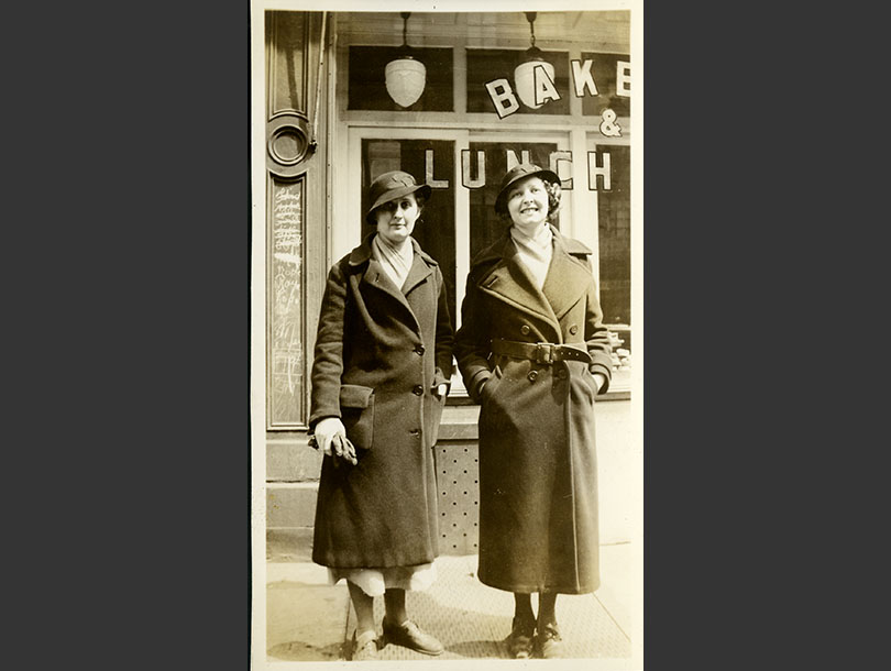 Two White, female nursing students standing outside a storefront in winter coats and cloche hats.