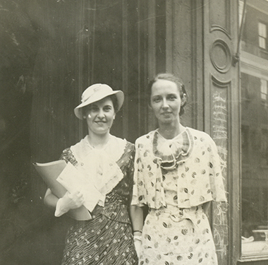 Two White, female students in calf-length print dresses standing in front of a store.