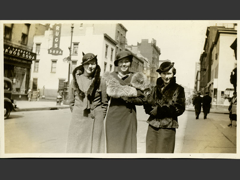 3 White female nursing students in fur-trimmed coats and cloche hats standing on a Manhattan street.