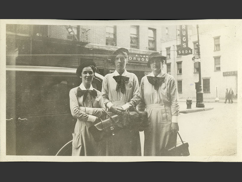 3 White female nursing students in uniform dresses and hats standing on a Manhattan street corner.