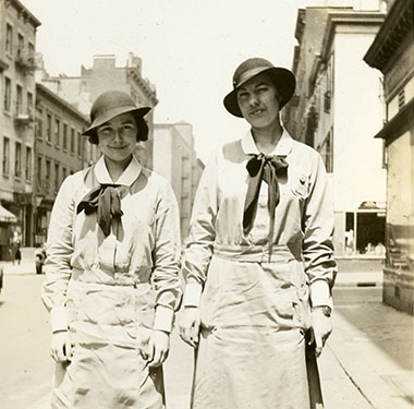 Two female nursing students in uniform dresses and cloche hats posing on a Manhattan sidewalk.