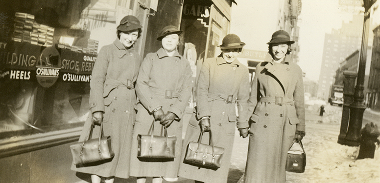 Four White, female nurses in matching winter coats, hats, and nurses' bags, standing in front of a store.