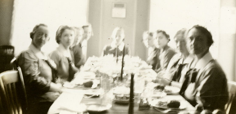 Eight nurses in matching uniforms sitting at a long table for a meal.