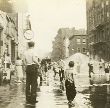 Children playing on a lower Manhattan street under an opened water sprinkle.