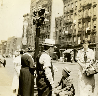 White, female nurse in uniform next to a street peddler's cart on Houston Street, Lower Manhattan.