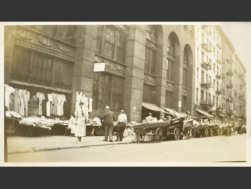 White, female nurse standing near several pushcarts on a street in Lower Manhattan.