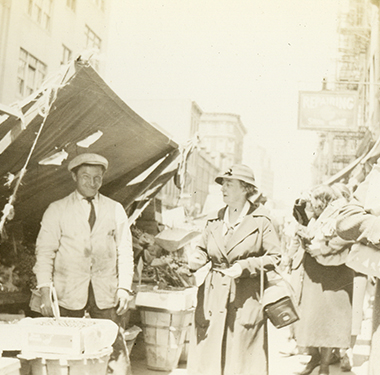 Female nurse in coat and cloche hat making a purchase from a man at a pushcart in Lower Manhattan.