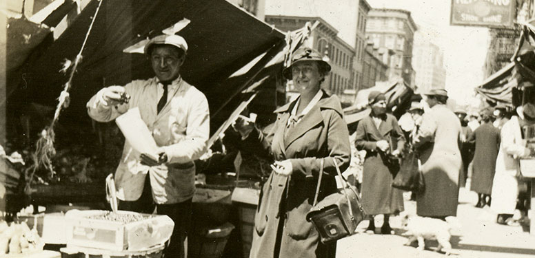 Female nurse in coat and cloche hat making a purchase at a pushcart from a man in Lower Manhattan.