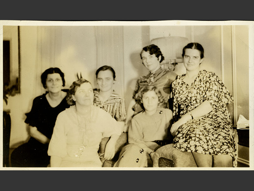 6 women smiling and sitting closely together in a living room.