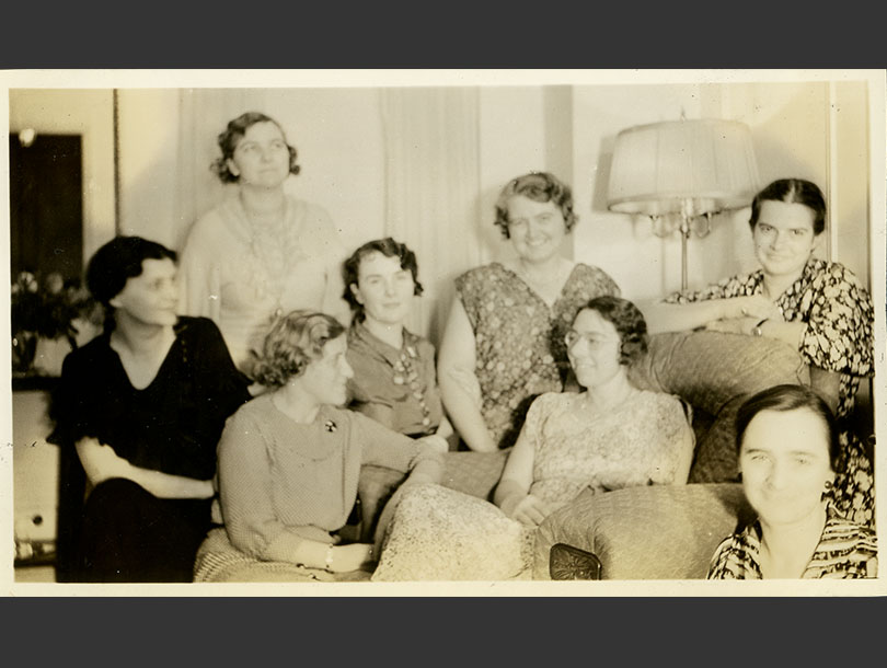 8 women smiling and sitting closely together in a living room.