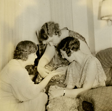 Three women sitting together in a living room, one reading the palm of another.