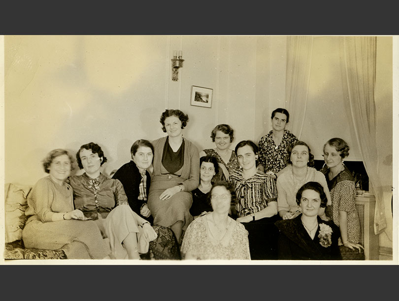 12 women posing, smiling, and sitting closely together in a living room.