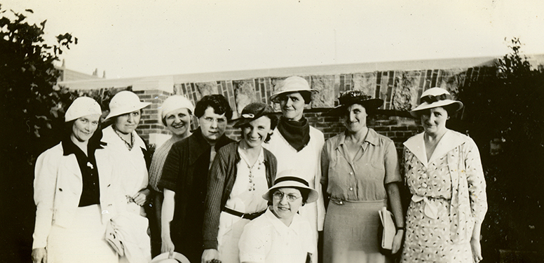 Group portrait of nine White women dressed up and standing near a wall.