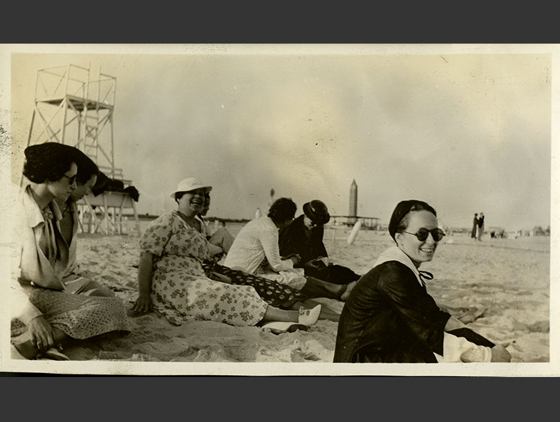 Seven women in dresses sitting on Jones Beach, life guard stand and obelisk water tower in background.