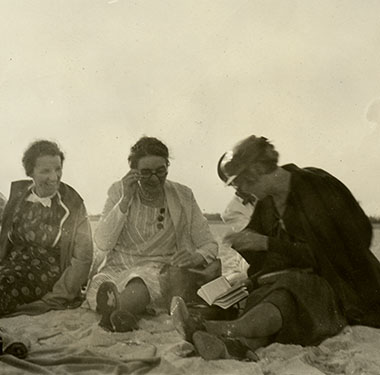 Seven smiling women in dresses sitting on Jones Beach, some are laughing while looking at a booklet.