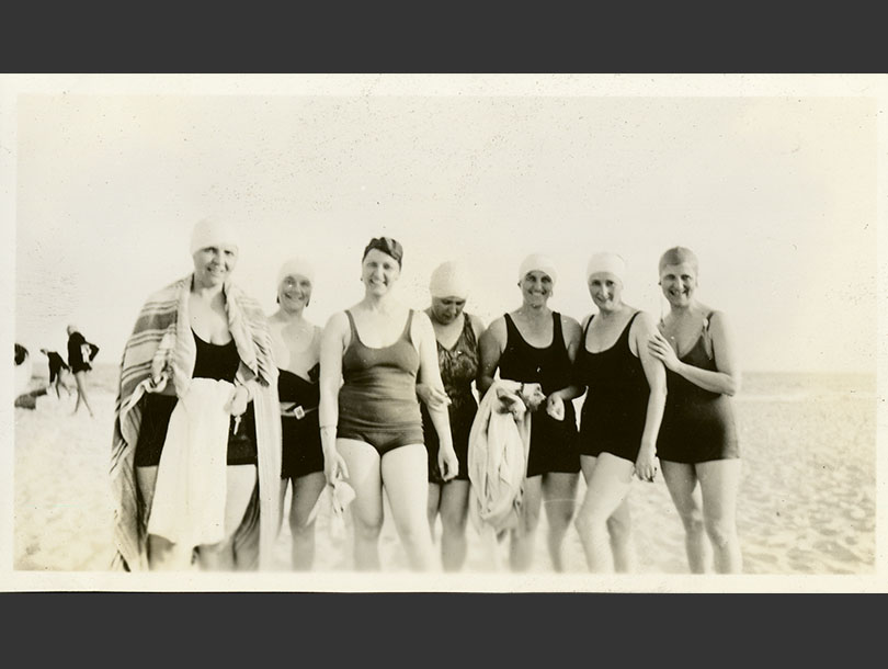 Posed group of seven women in one-piece swimsuits and bathing caps at Jones Beach.
