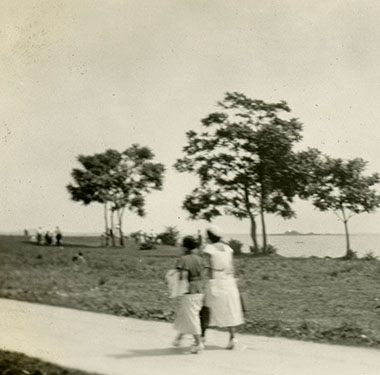 Two women in heeled-shoes walking along a paved path at the seashore.