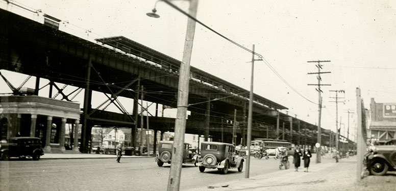 City street showing electricity poles, early 1930s cars, and an elevated train line.