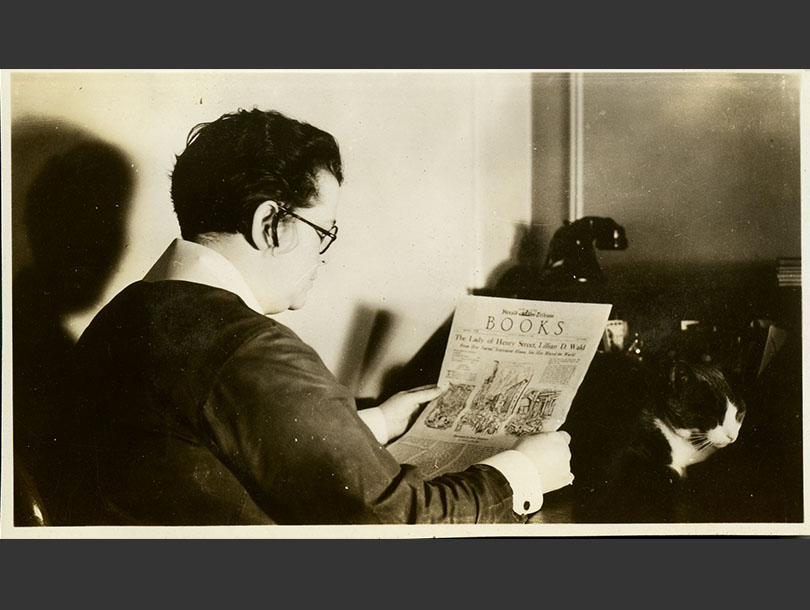 Profile view of a White, woman reading the <em>Herald Tribune<em> at a desk, nearby a cat and telephone.