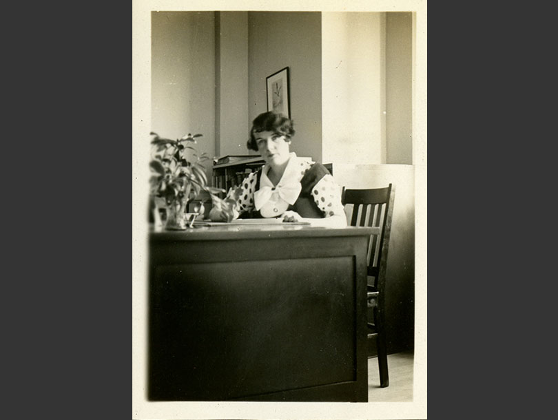 A White woman sitting behind a desk in an office.