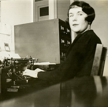 A White woman seated at desk, using a manual typewriter. Filing cabinet in background.