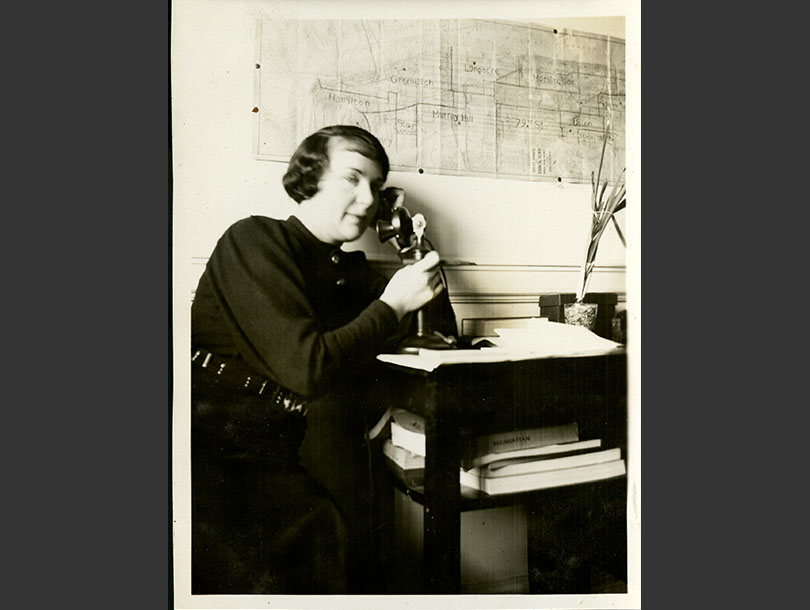 White woman sitting at a table, holding 1930s telephone with her right hand, earpiece at her left ear. Map of VNS districts on the wall.