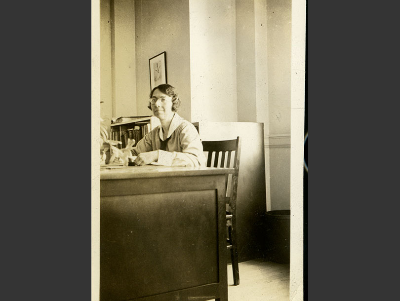White, female nurse with glasses in a nursing uniform, sitting behind a desk in an office.