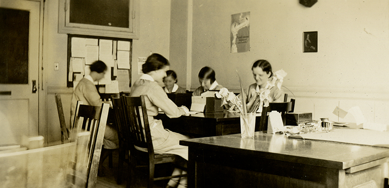 Five female nurses in uniforms working at desks in an office. Bulletin board hanging on the back wall.