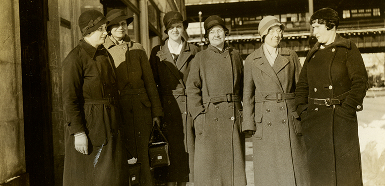 Six White female nurses in overcoats and cloche hats, Gun Hill elevated rail line in background.