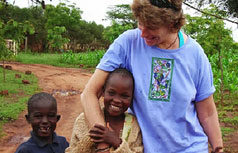 White woman walks with 2 smiling African children.