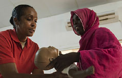 African America woman hands an infant sized mannequin to an African woman.
