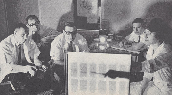 Four seated White men in lab coats look on as a White woman points towards a back lit board.