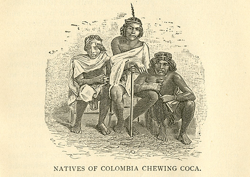 Three native Columbians in traditional dress sitting chewing coca leaves.
