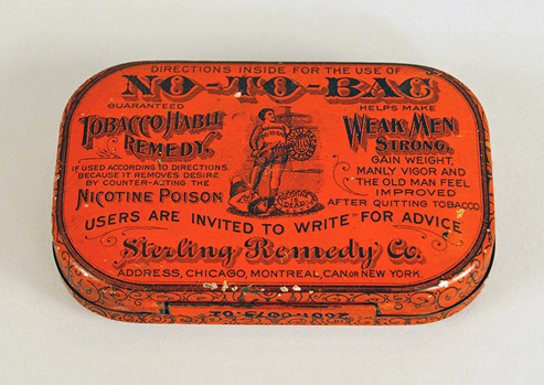 Photograph of the top of an orange anti-tobacco tin with advertisement engraved on it.